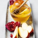 Rosh hashanah (jewish holiday) concept: honey, apple and pomegranateRosh hashanah (jewish holiday) concept: honey, apple and pomegranateRosh hashanah (jewish holiday) concept: honey, apple and pomegranate