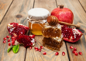 Honey with pomegranate on a old wooden background